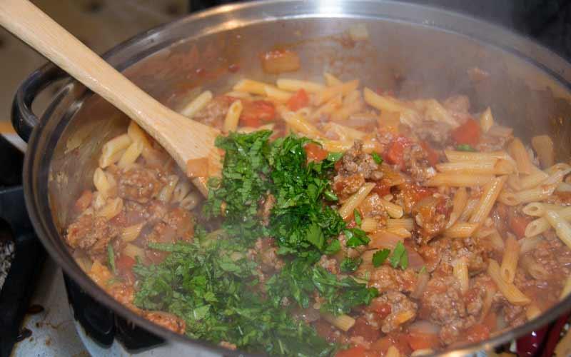 Stirring herbs into lamb ragù