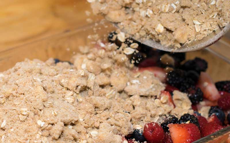 Spreading the crisp topping across the berries