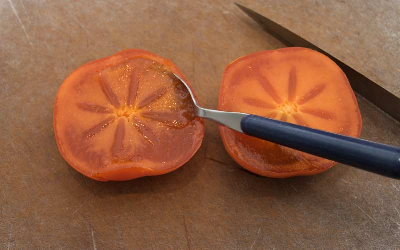 Persimmons being scooped
